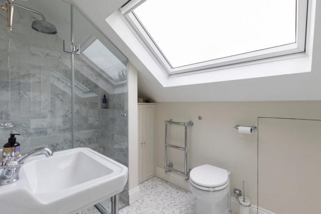 Дизайн ванной со скошенным потолком в классическом стиле с мраморной плиткой