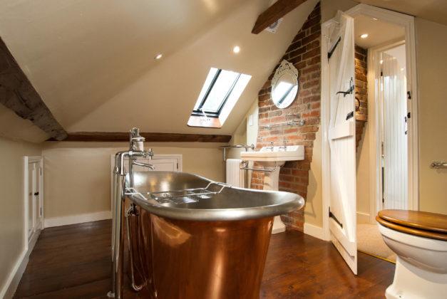 Ванная комната в мансарде в стиле кантри с бежевыми стенами и темным паркетным полом