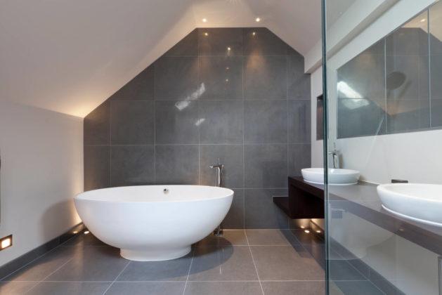 Ванная комната с аттиковой стеной в современном стиле с настольной раковиной и коричневой столешницей