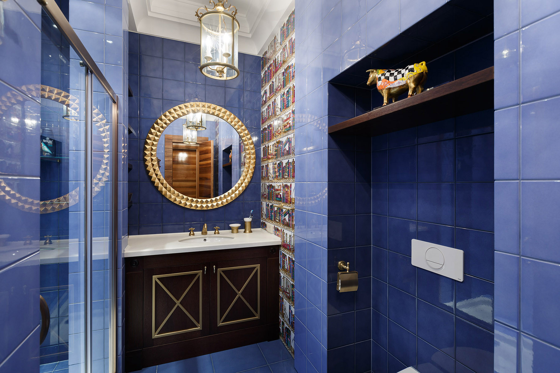 Темно-синие пол и стены, детали золотистого цвета в ванной
