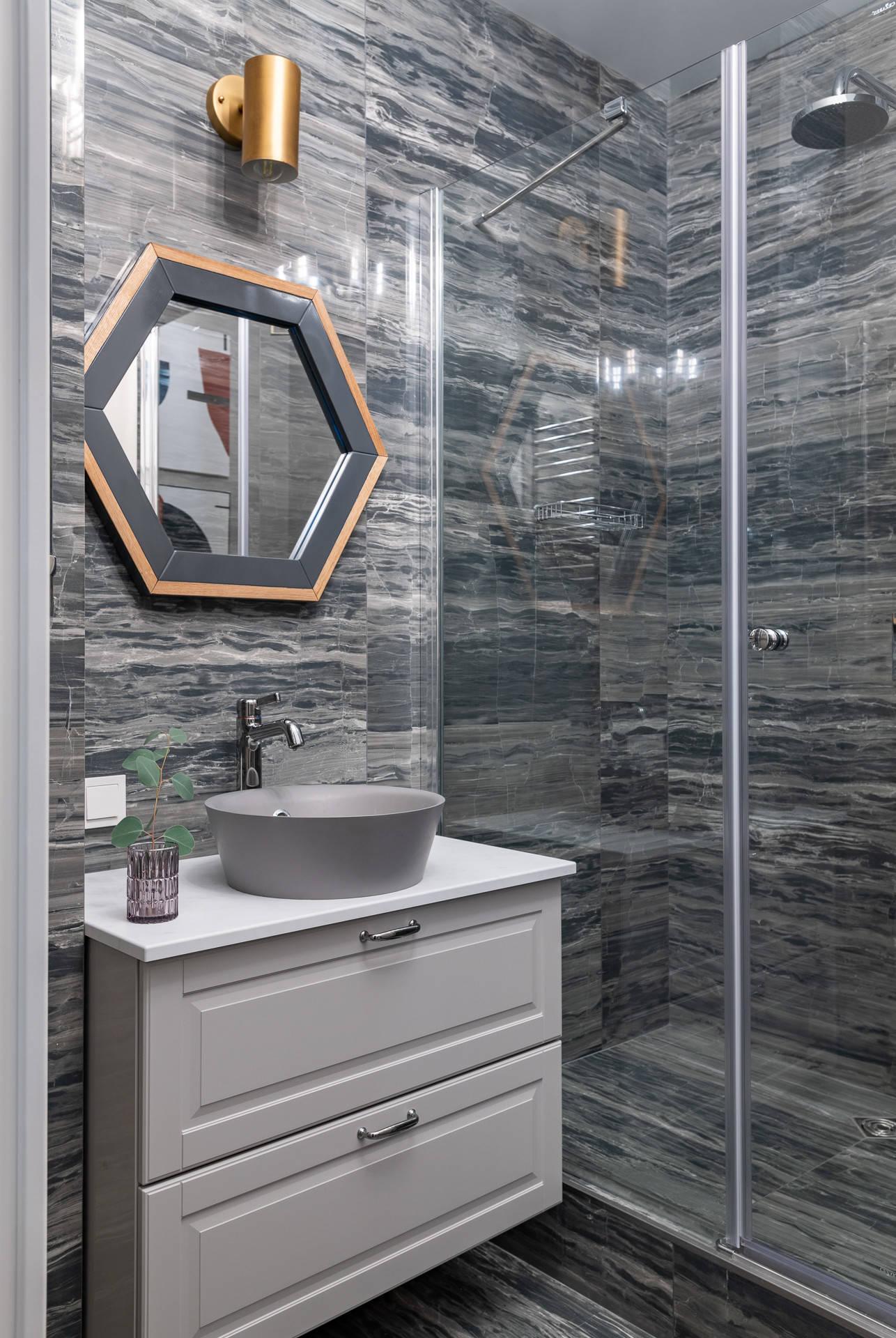 Серые стены, темный пол и темная раковина в ванной комнате