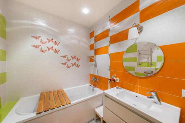 Ванная в ярких оранжево-зеленых тонах с изображением бабочек на стенах