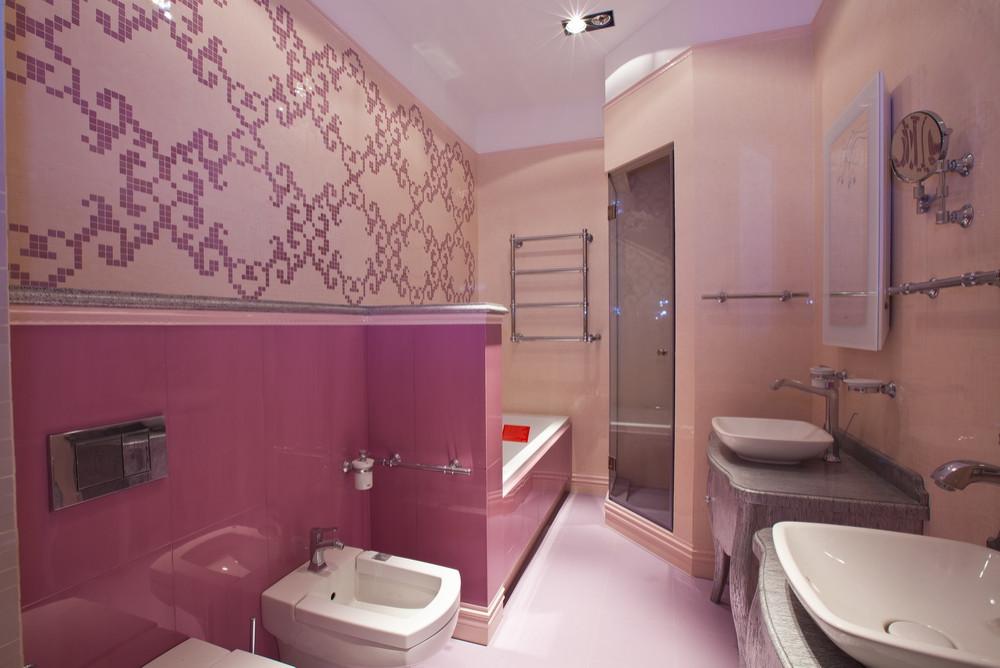 Ванная комната с серыми фасадами, гидромассажной ванной, душевой комнатой, керамической плиткой, розовыми стенами, полом из керамической плитки, настольной раковиной, столешницей из дерева, розовым полом, душем с распашными дверями и серой столешницей