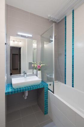 Ванная комната в современном стиле с недорогим дизайном, серой плиткой, серым полом, ванной в нише, душем над ванной и настольной раковиной