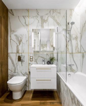 Ванная комната в современном стиле с недорогим дизайном, плоскими фасадами, белыми фасадами, полом из керамогранита, коричневым полом, ванной в нише, душем над ванной, раздельным унитазом, белой плиткой, монолитной раковиной и открытым душем