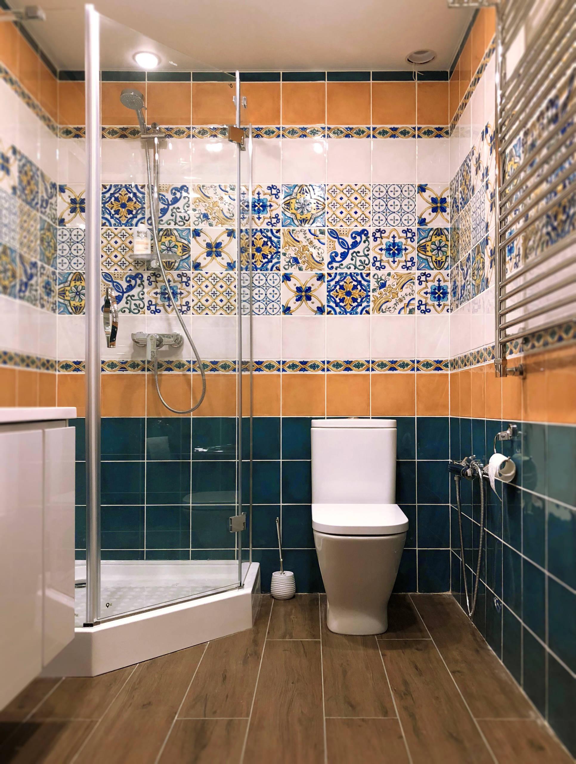 Темно-зеленая плитка со светлым полом и узорами на стенах в ванной комнате