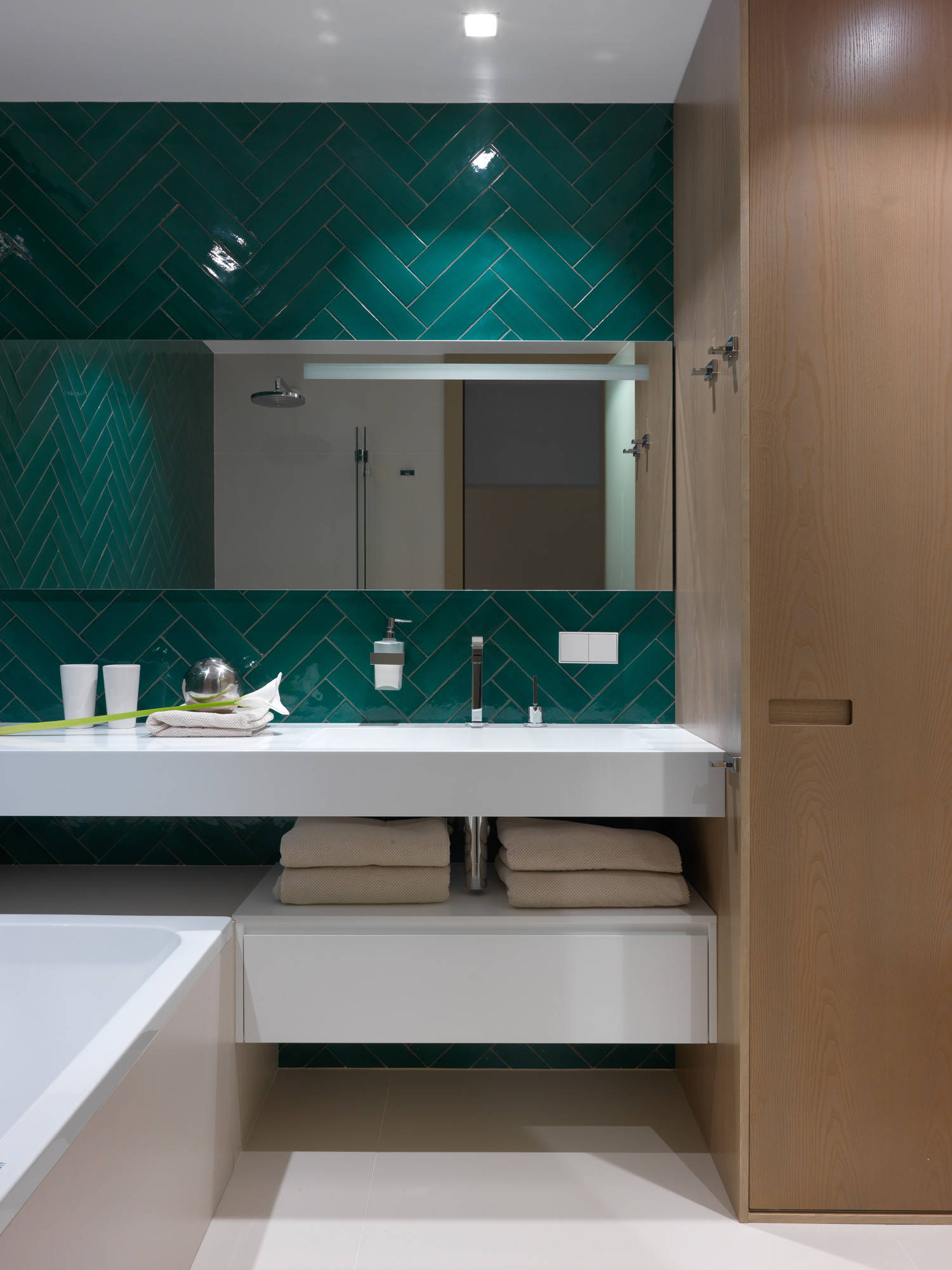 Темно-зеленая плитка на стенах ванной и белый пол