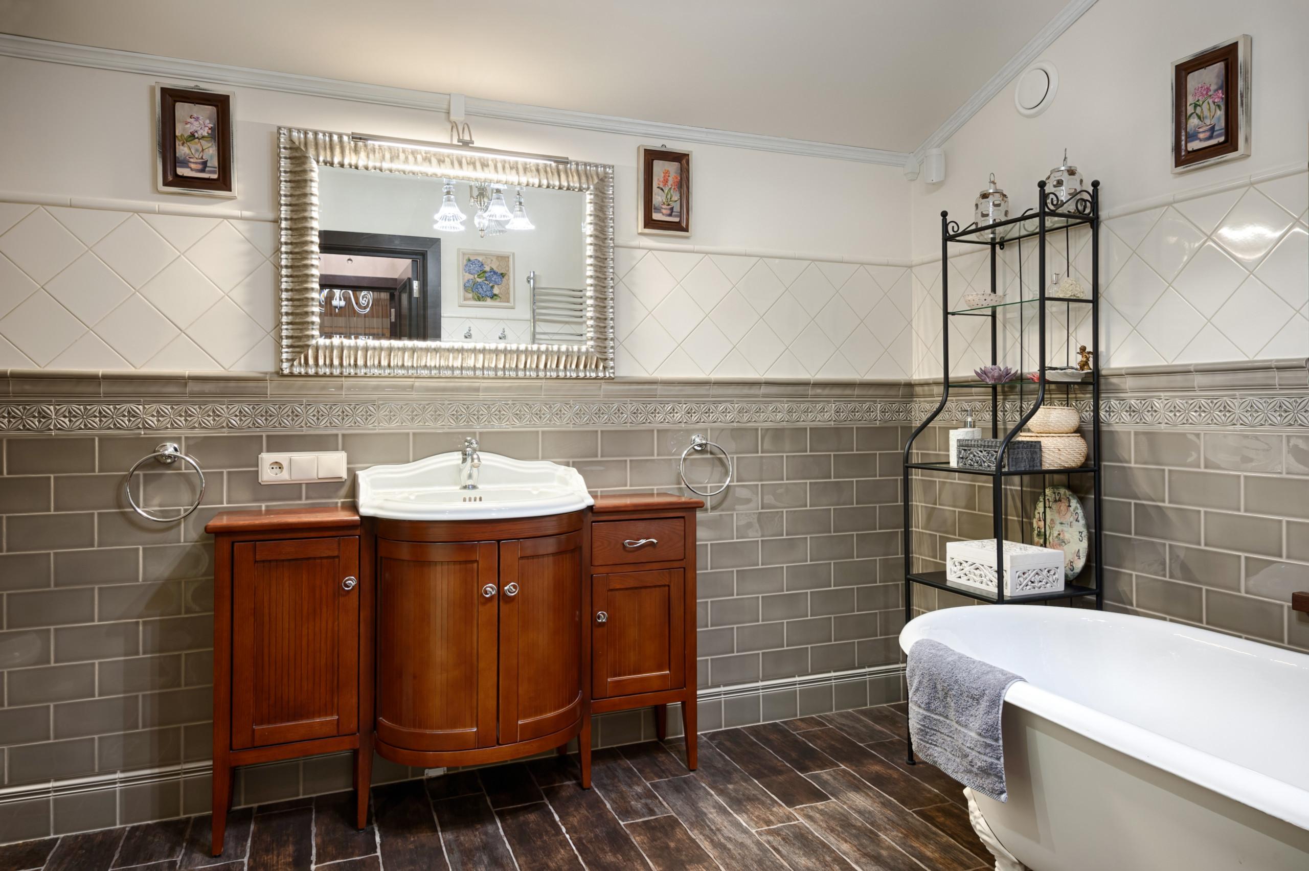 Темно-серая плитка в сочетании с белой ванной, деревянной мебелью и коричневым полом