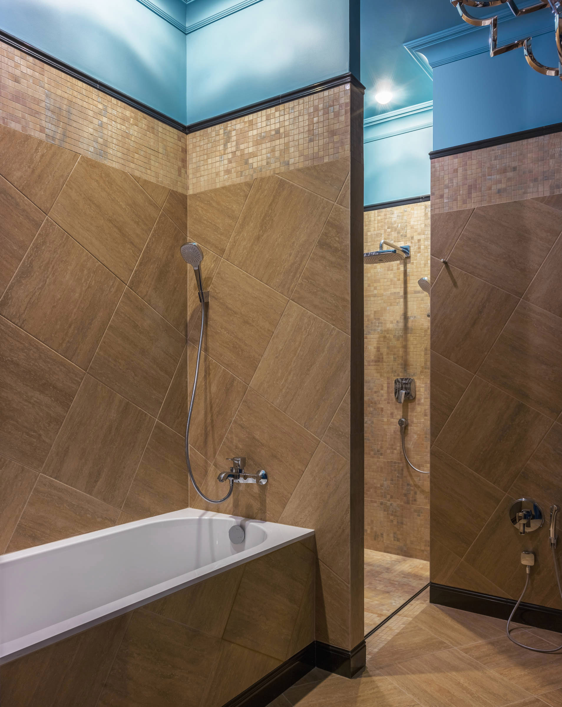 Сочетание коричневой плитки и голубого потолка в интерьере ванной