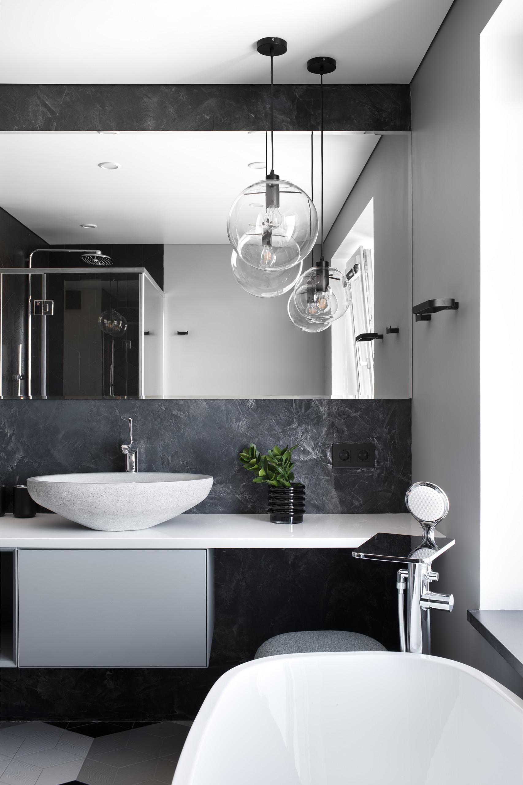 Темно-серая плитка на стенах и полу ванной и белая сантехника