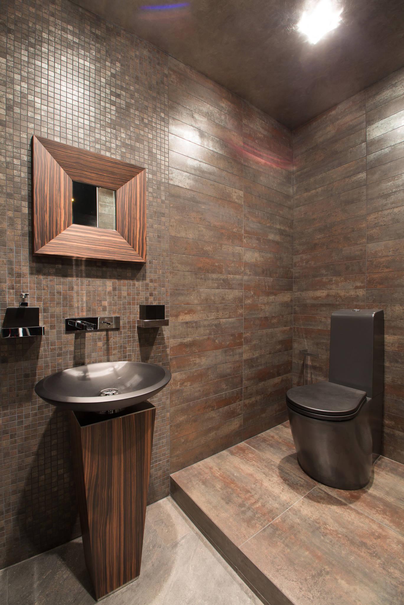 Стильная темно-коричневая плитка в ванной комнате с черным унитазом и черной раковиной