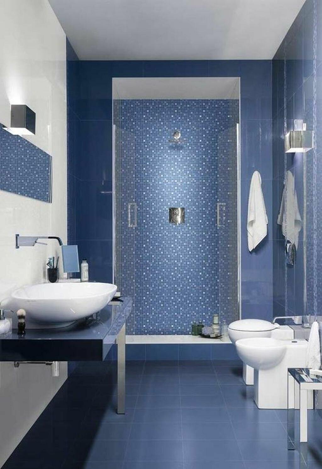Темно-синяя плитка на полу и на стенах ванной с белой сантехникой