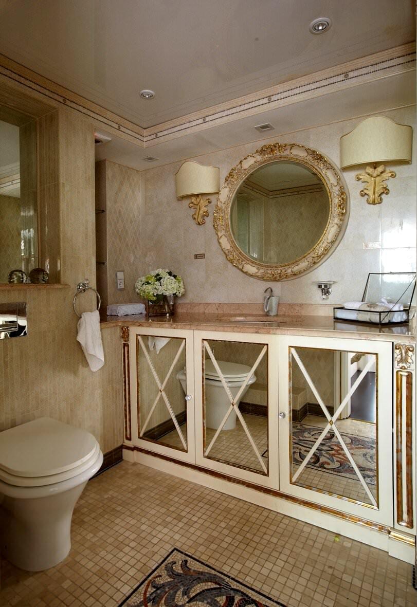 Туалет в классическом стиле с зеркальными дверцами шкафчиков