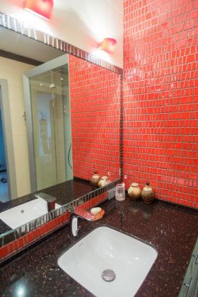 Ванная комната в современном стиле с красными стенами и столешницей из искусственного камня