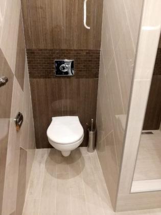 Маленький туалет в скандинавском стиле с коричневой плиткой, керамической плиткой, коричневыми стенами, полом из керамогранита и бежевым полом