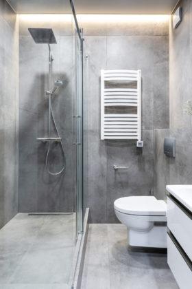 Маленький туалет в современном стиле с серой плиткой, керамогранитной плиткой, серыми стенами, полом из керамогранита, подвесной раковиной и серым полом