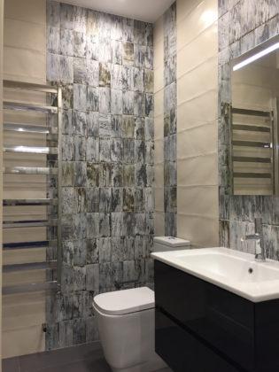 Туалет среднего размера в стиле лофт с унитазом-моноблоком, серой плиткой, керамической плиткой, серыми стенами, полом из керамогранита, подвесной раковиной, серым полом и белой столешницей