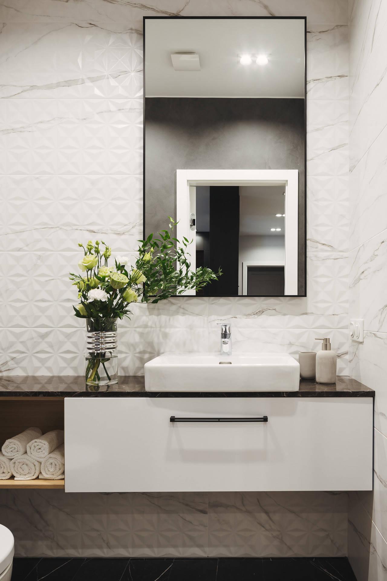 Туалет в современном стиле с плоскими фасадами, белыми фасадами, белой плиткой, белыми стенами, настольной раковиной, черным полом и черной столешницей