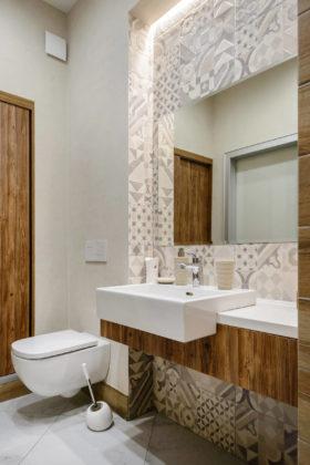 Туалет в современном стиле с серой плиткой, белой плиткой, цементной плиткой, бежевыми стенами, настольной раковиной, бежевым полом и белой столешницей