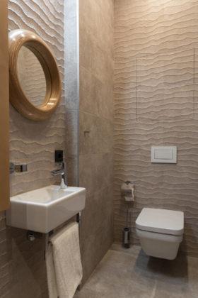 Туалет среднего размера в современном стиле с бежевой плиткой, керамогранитной плиткой, бежевыми стенами, полом из керамогранита, подвесной раковиной и бежевым полом