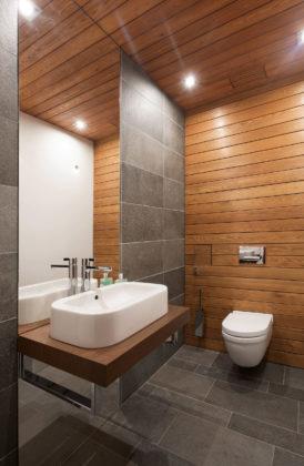 Маленький туалет в современном стиле с серой плиткой, плиткой из сланца, разноцветными стенами, полом из сланца, настольной раковиной, столешницей из дерева, серым полом и коричневой столешницей