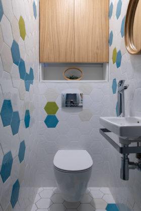 Туалет в современном стиле с белой плиткой, разноцветной плиткой, подвесной раковиной и белым полом