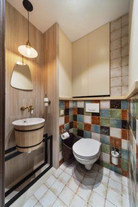 Туалет в современном стиле с бежевой плиткой, разноцветной плиткой, консольной раковиной и белым полом