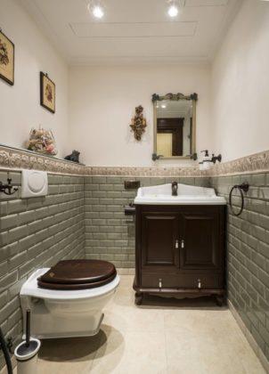 Туалет в классическом стиле с зеленой плиткой, плиткой кабанчик, бежевым полом, разноцветными стенами и консольной раковиной