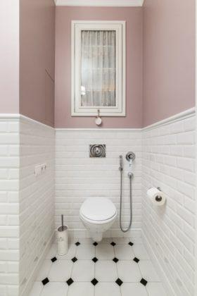 Туалет в классическом стиле с белой плиткой, плиткой кабанчик, розовыми стенами и разноцветным полом