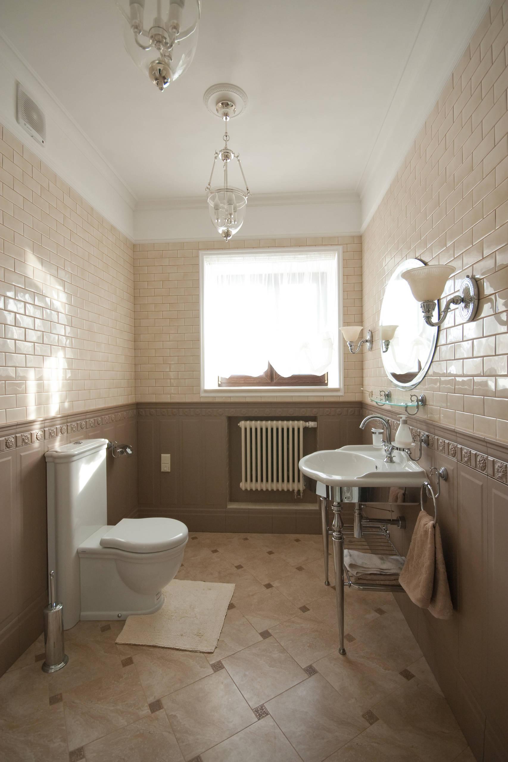 Туалет в классическом стиле с унитазом-моноблоком, бежевой плиткой, коричневой плиткой, консольной раковиной и коричневым полом