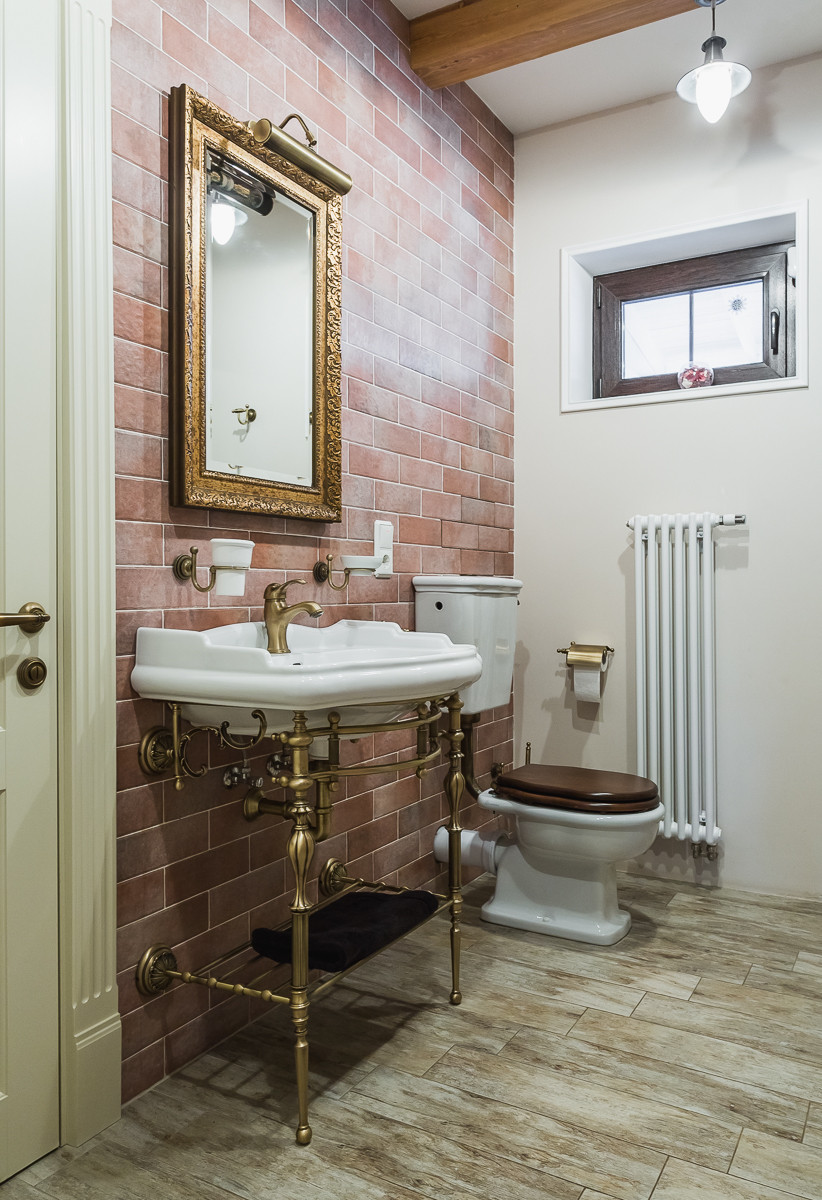 Туалет среднего размера в классическом стиле с унитазом-моноблоком, керамогранитной плиткой, разноцветными стенами, полом из керамогранита, консольной раковиной и коричневой плиткой