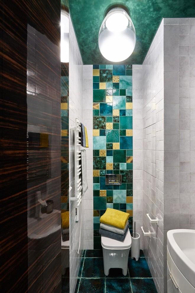 Туалет в современном стиле с белыми фасадами, раздельным унитазом, белой плиткой, зеленой плиткой, серой плиткой, накладной раковиной и синим полом