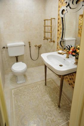 Туалет в классическом стиле с узорным полом и белой раковиной