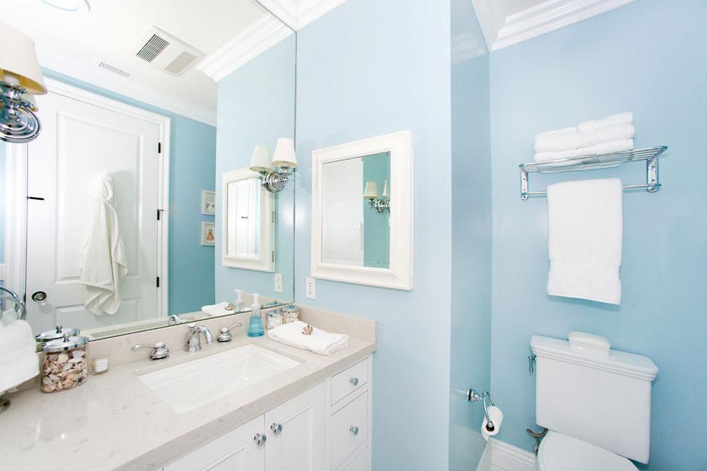 Небесно-голубая ванная с белым унитазом и белой раковиной