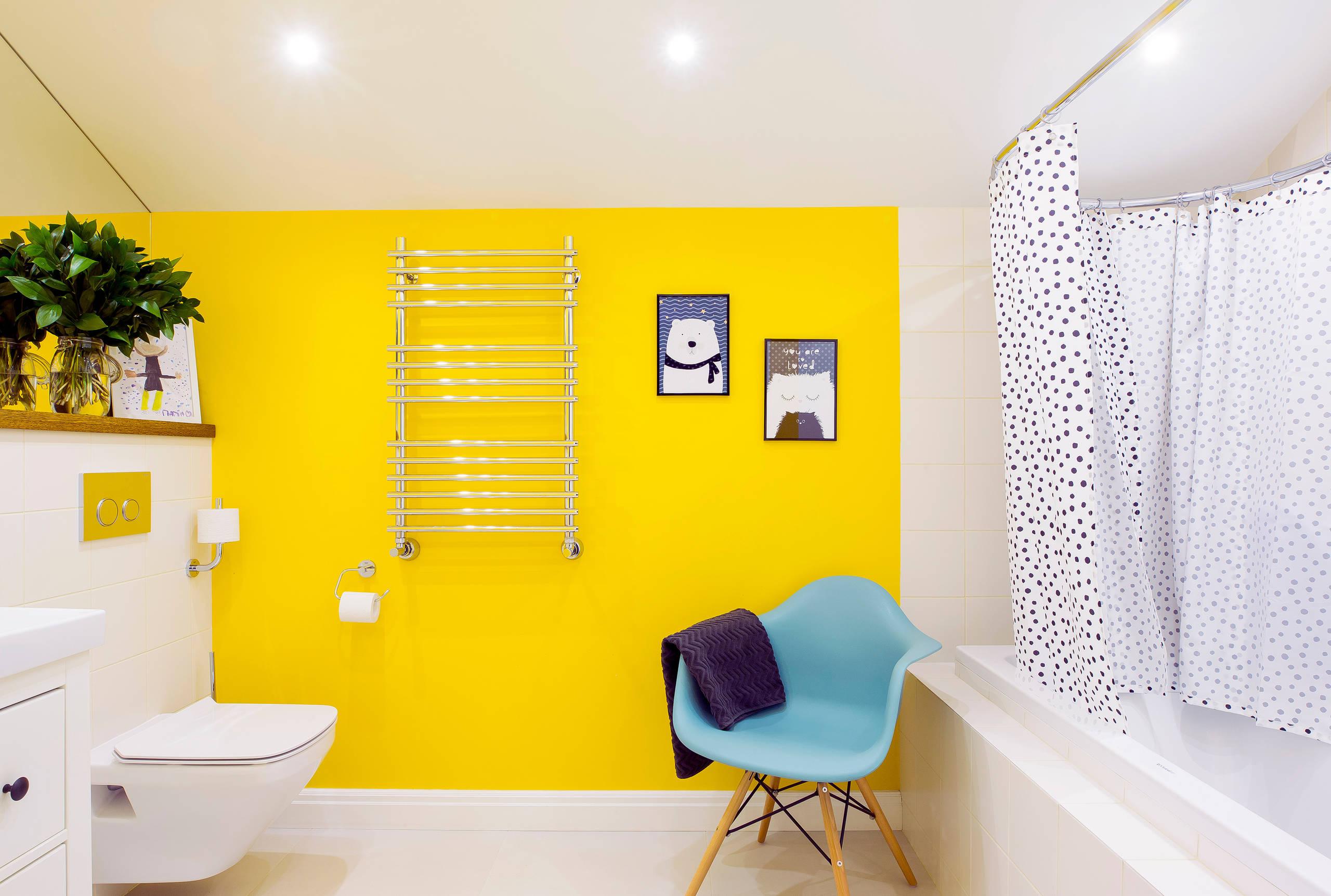 Ярко-желтая ванная с белой ванной, белым унитазом и белой раковиной